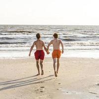 tiener geniet van joggen langs het strand foto