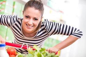 vrouw genieten van winkelen bij supermarkt foto