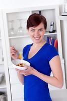jonge vrouw die van een gezonde groene salade geniet foto