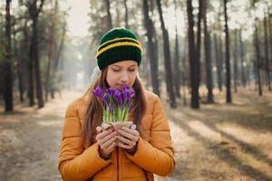 gelukkige vrouw genieten van geur van Lentebloemen foto