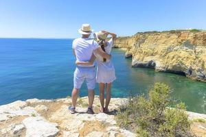 paar genieten van het uitzicht op de oceaan vanaf een klif foto