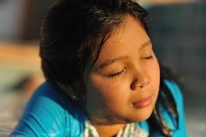 klein meisje genieten van de zon op haar gezicht foto