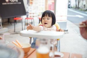 het Japanse babymeisje geniet van bij een openluchtrestaurant foto