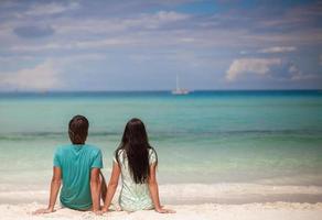 jong koppel genieten van elkaar op witte zandstrand foto