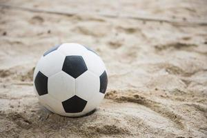 voetbal op zandstrand foto