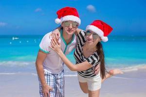 portret van een jong koppel in santa hoeden genieten van strandvakantie foto