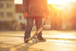 kind met skateboard op straat bij zonsondergang licht