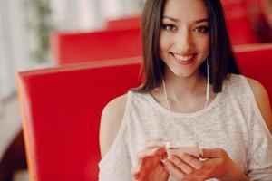 mooi jong meisje geniet van telefoon en tablet foto