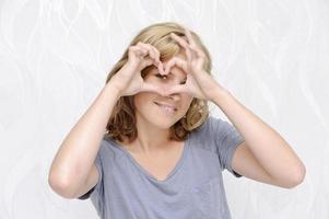 glimlachende jonge vrouw die hart met vingers maakt