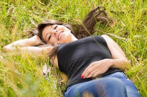 mooi donkerbruin jong meisje dat op groen gras rust