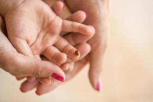 moeders hand cupping childs hand waarop lieveheersbeestje zit