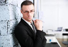 zakenman die zich dichtbij bakstenen muur bevindt foto
