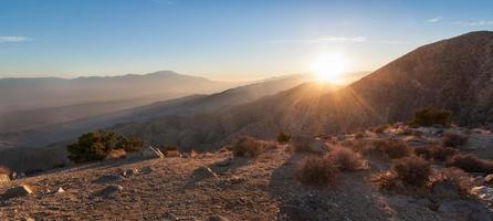 zonnestralen over bergketen in de woestijn foto