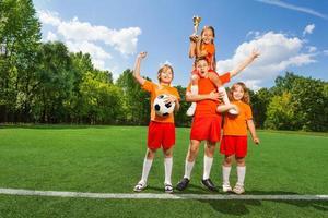 gelukkige kinderen met gouden beker staan in piramide foto
