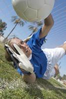 jonge vrouwelijke voetbalkeeper duiken om een doelpoging te blokkeren
