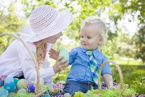 schattige jonge broer en zus genieten van hun paaseieren buiten