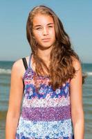gelukkig meisje met lang bruin haar genieten van het verfrissende strand. foto