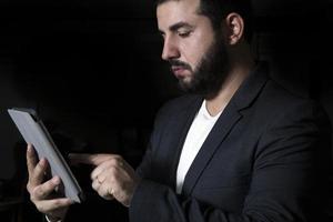 schemerig licht zakenman met pad in de hand foto