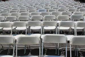 rijen opvouwbare witte stoelen foto