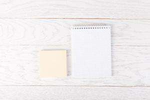 Kladblok met sticker papier op tafel foto