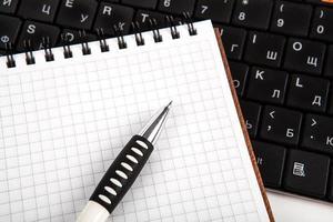 pen op een notebook in een cel en toetsenbord foto