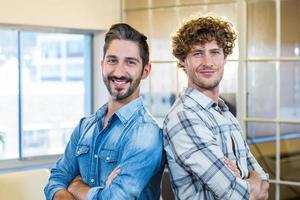 glimlachend team staande armen gekruist foto
