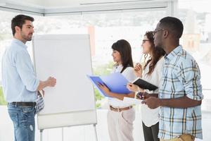 man presenteren en collega's maken van aantekeningen foto