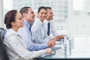 zakenvrouw glimlachend in de camera terwijl haar collega's luisteren foto