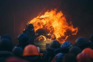 brandende auto tijdens oproerbestrijding foto