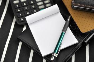 pen op blanco notitieblok met rekenmachine foto