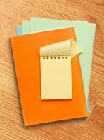 open gele notitieblok op gekleurd papier foto