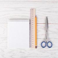 Kladblok met potlood, liniaal en schaar op tafel foto