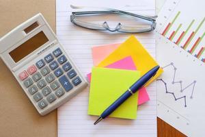 notitie boek en grafiek op houten tafel met rekenmachine foto