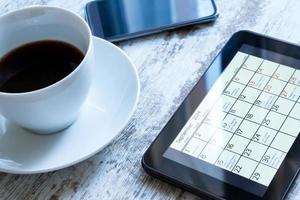 het controleren van maandelijkse activiteiten in de kalender op de tablet foto
