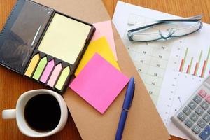 notitie boek en grafiek op houten tafel met koffie foto
