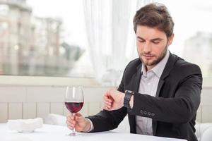 aantrekkelijke jonge zakenman wacht op zijn cliënt foto