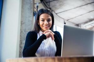 Glimlachende zakenvrouw in café foto