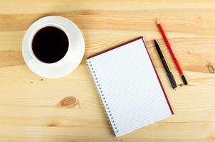notebook pen en kopje koffie in houten tafel foto