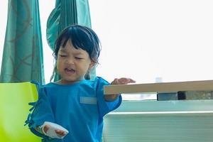 ziekte Aziatische kinderen zitten op een stoel in het ziekenhuis foto