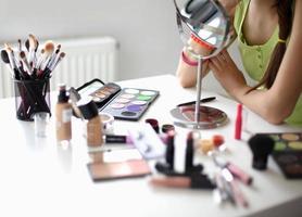 jonge mooie vrouw die make-up in de buurt van spiegel, zittend op foto
