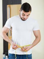 man zijn biceps en lichaam meten foto