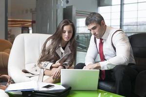 zakenman en zakenvrouw tijdens bijeenkomst met laptop foto