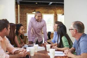 mannelijke baas aanspreken van kantoorpersoneel tijdens vergadering
