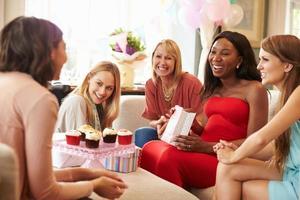 groep vrouwelijke vrienden die voor babydouche thuis samenkomen foto
