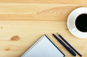 notebook pen en kopje koffie in houten tafel