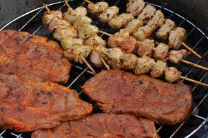 barbecuespiesen en grillsteaks op een grill foto