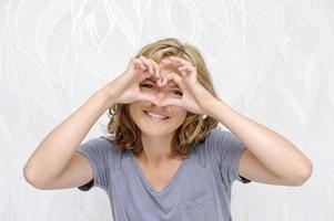 glimlachende jonge vrouw die hart met vingers maakt foto