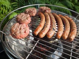 worstjes en beefburgers grillen op een barbecue foto