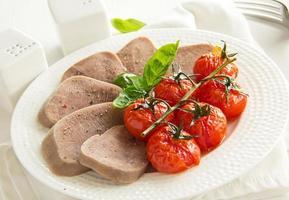 tong van gekookt rundvlees met gegrilde tomaten. foto