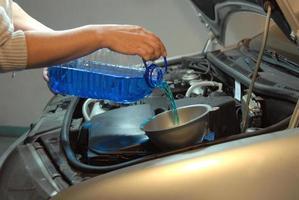 het vullen van de ruitensproeiervloeistof van een auto foto